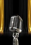 Silbernes Mikrofon mit schwarzen Goldtrennvorhängen Lizenzfreie Stockfotos