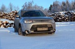 Silbernes Mitsubishi-Outlanderauto auf dem Schneefeld Lizenzfreie Stockbilder