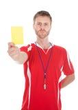 Silbido que sopla del árbitro mientras que muestra la tarjeta amarilla Foto de archivo libre de regalías