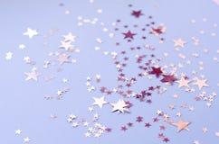 Silbrige Sterne von verschiedenen Größen auf einem blauen Hintergrund stockfotos