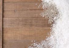 Silbrige Weihnachtsschneeflocken-Verzierung in Snowbank auf rustikalem hölzernem Hintergrund mit Raum oder Raum für Kopie, Text, W Stockfotografie