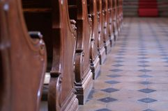 Silence. Empty pews in the church, shallow dof. Free space for text on the right side Royalty Free Stock Photo