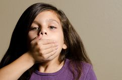 Silence!. A little girl with her hand over her mouth Royalty Free Stock Photos
