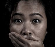 Silence. An asian woman silenced by a hand Stock Photo
