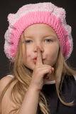 Silence. Little girl keeping finger at her mouth as silence or secret sign, closeup portrait on black background stock photos