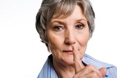 Silence. Photo of elderly female showing gesture of silence over white background Royalty Free Stock Photography