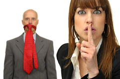 Silence. Businesswoman asking for silence and man in the background with tie in is mouth Royalty Free Stock Image