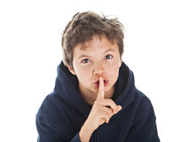Silence. Boy pointing his finger at his lips gesturing silence. Copy Space to the left Royalty Free Stock Images