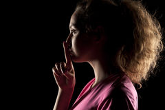 Silence gesture. Young woman with her face in shadow holding finger on her lips royalty free stock photos
