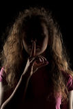 Silence gesture. Young woman with her face in shadow holding finger on her lips royalty free stock image