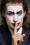Silence is gold. Portrait of businessman with theatrical makeup gesturing silence stock photo