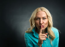 Silence hand sign. Blonde woman showing silence hand sign Stock Photography