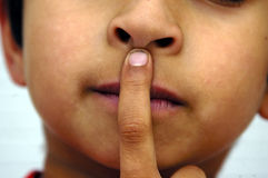 Silence Please. A kid placing his hands on his lips Stock Image