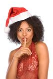 Silence please!. Attractive woman in Christmas outfit with finger on her lips Royalty Free Stock Photos