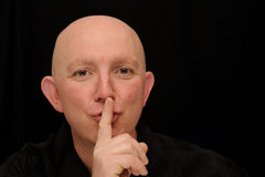Silence Please. A man gesturing with his finger on mouth for silence Stock Photography