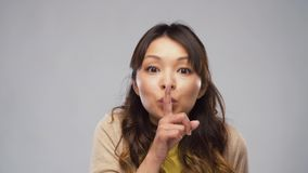 Asian woman making shush gesture. Silence, privacy and silence concept - asian woman making shush gesture over grey background stock footage
