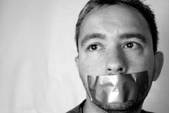 Silenced. Man with tape across his mouth stock photography