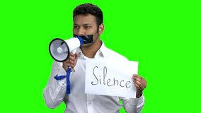 Silenced businessman on green screen. Man with taped mouth can not speak. Censorship and freedom of speech stock video