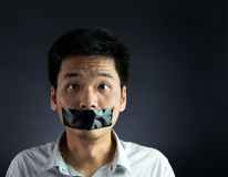 Silenced. Man with black tape over his mouth on black background royalty free stock image