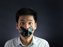 Silenced. Man with black tape over his mouth on black background royalty free stock images