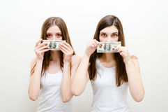 Silenced by money. Two beautiful young women showing money Royalty Free Stock Image