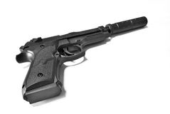Silenced Pistol. An isolated image of a dusty toy pistol with silencer Royalty Free Stock Image