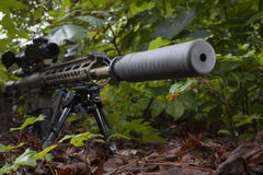 Silenced weapon. Camoflauge modern sporting rifle with a silencer on the barrel Royalty Free Stock Images