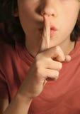 Silencie el gesto, el muchacho pide guarda secreto importante foto de archivo