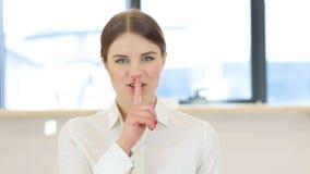Silencio, finger en los labios de la mujer en oficina foto de archivo libre de regalías