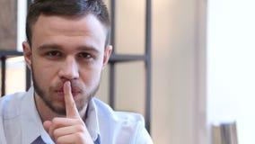 Silencio por favor, finger en los labios del hombre joven almacen de video