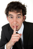 Silent. Portrait of a young man making a handsign to be silent Royalty Free Stock Photo