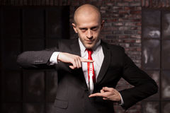 Silent assassin, oriental martial arts in action. Bald contract murderer in suit and red tie holds combat knife. Fighting knife is a dangerous weapon in right Stock Photo