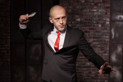 Silent assassin, oriental martial arts in action. Bald contract murderer in suit and red tie holds combat knife. Fighting knife is a dangerous weapon in right Royalty Free Stock Image