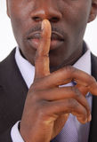The Silent Business. This is an image of businessman with his hands on his lips. This posture implies secrecy, illegal business, trust etc Royalty Free Stock Photos