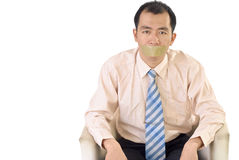 Silent businessman. With tape on mouth sit on white background Stock Photos