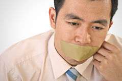 Silent businessman of Asian. Closeup portrait with tape on mouth Royalty Free Stock Photos