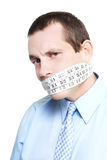 Silent businessman showing measured restraint. With a tape measure tied around face in a business challenge with numbers concept on white background Stock Photography