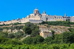The Silent City and Ruined Chapel. The silent city of Mdina, Malta against the background of a blue sky. In the fore ground is a ruined chapel Stock Photos