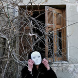 Silent command. Grotesque white mask figure and haunted house window with tangled overgrown plants and creepy dummy doll hand Royalty Free Stock Photography