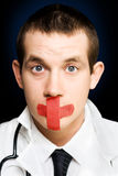 Silent handsome doctor with cross bandage on face Stock Photography