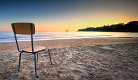 A Silent Invite. A broken and old chair left on the sand at the beach pointed to the sunset behind a hill. The concept of loneliness and missing Royalty Free Stock Images