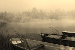 Silent morning with boats on a foggy lake  Stock Photos
