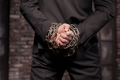 Silent murderer hands in iron chain, back view Stock Photo
