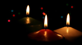 Silent Night. Three Christmas candles up close, with festive lights in the background Stock Images
