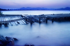 Silent night. A damage wooden pier in a lake on a beautiful night, taken at Dongqian Lake, Ningbo, China Royalty Free Stock Photos