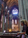 Silent prayer. Young girl is praying silently inside big cathedral Royalty Free Stock Photos