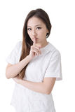 Silent sign. Smiling Asian nurse give an silent sign, closeup woman portrait isolated on white background Stock Photo