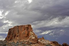 Silent soldier granite outcrop surrounded by storm clouds, out-back north western Australia. Small granite breakaway in the northern goldfields of the east stock images