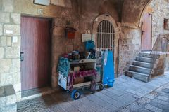 Silent streets of Jerusalem. A carriage with religious books stands in the Jewish quarter near a wall in the old city of Jerusalem. Jerusalem, Israel, August 18 stock photo