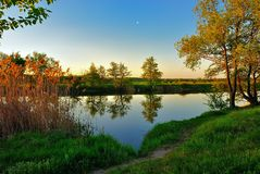 Silent summer evening by the river. Star in the evening sky over the quiet river Stock Image